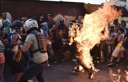 Opposition demonstrators set an alleged thief on fire during a protest against the government of President Nicolas Maduro in Caracas on May 20, 2017.  According to the Venezuelan Interior and Justice Ministry the victim, Orlando Figuera, 21, who was set on fire accused of being a chavist or a thief, remains at hospital with first and second degree burns in 80% of his body and several stab wounds.  / AFP PHOTO / CARLOS BECERRA / Venezuela OUT