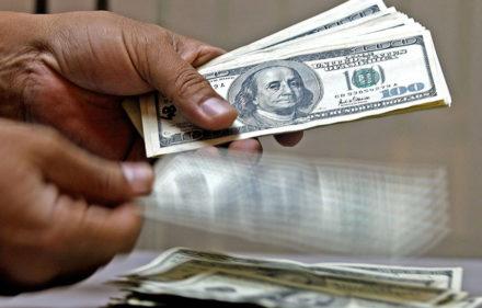Un empleado de una casa de cambio cuenta d-lares estadounidenses en Bogota el 22 de febrero de 2005. El precio del dolar en Colombia cay- al nivel de cotizaci-n de hace tres a–os, y se cotiza hoy en 2.312 pesos, consecuencia del aumento de las exportaciones y de las remesas del exterior.          AFP PHOTO/Luis ACOSTA