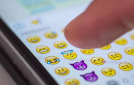 """ARCHIV - ILLUSTRATION - Eine Frau tippt am 24.08.2015 in M¸nchen (Bayern) auf das Display eines Smartphones, auf dem zahlreiche Emojis in der Nachrichten-App """"Whatsapp"""" zu sehen sind. Oxford Dictionaries haben erstmals ein Emoji zum Wort des Jahres gew‰hlt. Eher konservative Sprachpfleger mˆgen den Kopf sch¸tteln - doch die Wahl 2015 fiel auf das ber¸hmten ´Smileygesicht  mit den Freudentr‰nenª. Foto: Matthias Balk/dpa (zu dpa """"Oxford Dictionaries k¸rt Freudentr‰nen-Emoji zum Wort des Jahres"""" vom 17.11.2015) +++(c) dpa - Bildfunk+++"""