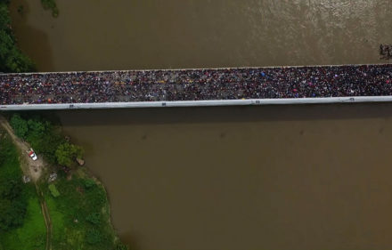 Aerial view of a Honduran migrant caravan heading to the US, on the Guatemala-Mexico international bridge in Ciudad Hidalgo, Chiapas state, Mexico, on October 19, 2018. - Honduran migrants who have made their way through Central America were gathering at Guatemala's northern border with Mexico on Friday, despite President Donald Trump's threat to deploy the military to stop them entering the United States. (Photo by PEDRO PARDO / AFP)